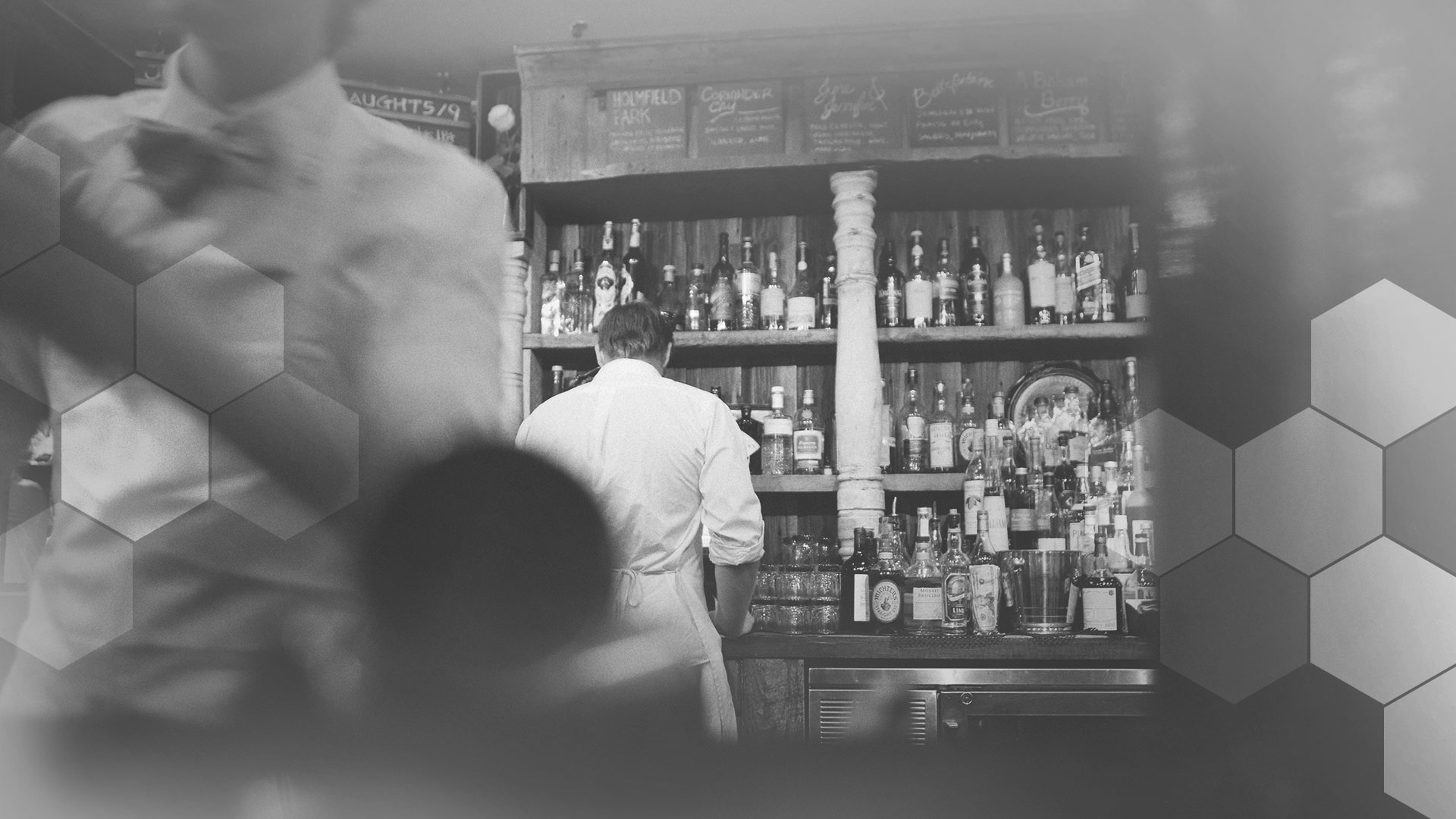 A monochrome scene at a busy restaurant bar.