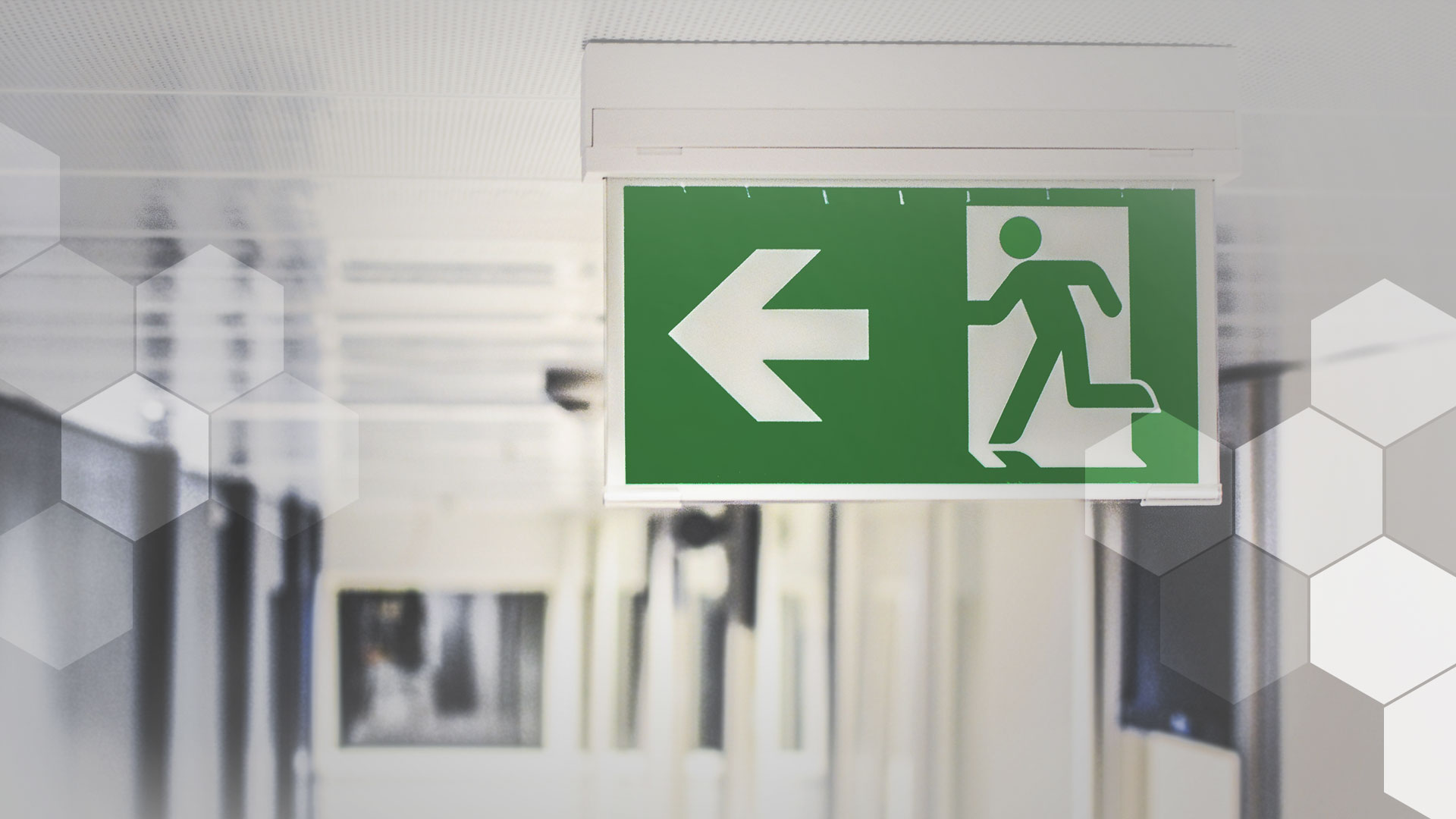 A photo of an emergency-exit sign on a corridor ceiling – because call center attrition is that bad.
